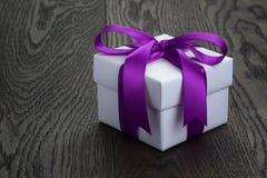 Caja de regalo con el arco de la cinta en la tabla de roble vieja Imagen de archivo libre de regalías
