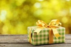 Caja de regalo con el arco de oro en un fondo de madera gris Foto de archivo