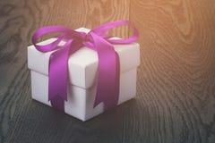 Caja de regalo con el arco de la cinta en la tabla de roble vieja Foto de archivo libre de regalías