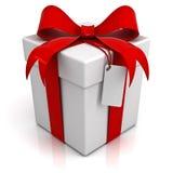 Caja de regalo con el arco rojo de la cinta y etiqueta en blanco en el fondo blanco Imagen de archivo libre de regalías