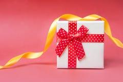 Caja de regalo con el arco rojo en fondo rosado y rojo brillante y festivo Imagen de archivo