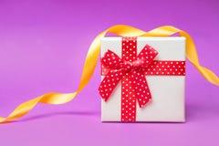 Caja de regalo con el arco rojo en fondo rosado y rojo brillante y festivo Fotos de archivo