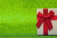 Caja de regalo con el arco rojo en fondo verde chispeante brillante y festivo Imagen de archivo libre de regalías