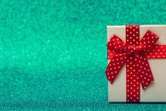 Caja de regalo con el arco rojo en fondo verde chispeante brillante y festivo Imagenes de archivo