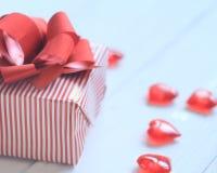 Caja de regalo con el arco rojo y corazones en fondo ligero Fotos de archivo libres de regalías