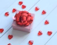 Caja de regalo con el arco rojo y corazones en fondo ligero Fotografía de archivo