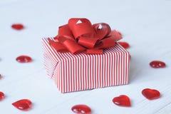 Caja de regalo con el arco rojo y corazones en fondo ligero Imagen de archivo libre de regalías