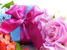 Caja de regalo con el arco rosado de la cinta y el fondo colorido hermoso de las flores Fotografía de archivo libre de regalías