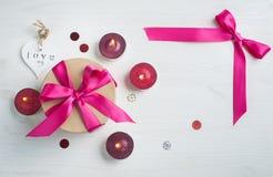 Caja de regalo con el arco rosado y las velas encendidas imagenes de archivo