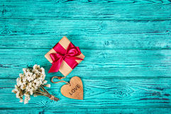 Caja de regalo con el arco y corazón de madera en un fondo de madera azul Copie el espacio Fotografía de archivo