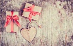 Caja de regalo con el arco y corazón de madera en una tabla de madera vieja Fotografía de archivo