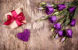Caja de regalo con el arco y las flores púrpuras Eustoma Corazón de mimbre St Día del ` s de la tarjeta del día de San Valentín Imagen de archivo