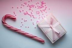 Caja de regalo con el arco y piruleta en fondo rosado fotos de archivo