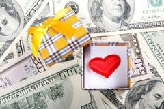 Caja de regalo con el corazón rojo en fondo del dinero Fotografía de archivo libre de regalías