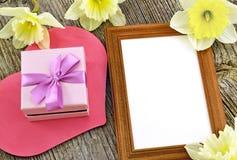 Caja de regalo con el marco de la foto en el fondo del tablero de madera Imágenes de archivo libres de regalías