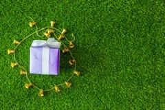 caja de regalo con la campana de oro en fondo de la hierba verde con Imagen de archivo