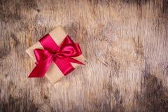 Caja de regalo con la cinta de satén en un fondo de madera Copie el espacio Fotos de archivo