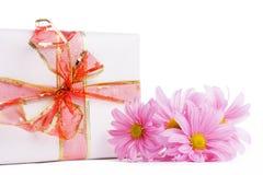 Caja de regalo con la cinta roja y los dasies rosados Imagenes de archivo