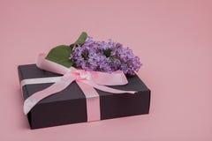 Caja de regalo con la cinta rosada en el fondo rosado, adornado con la lila Día del `s de la madre Día del ` s de la tarjeta del  Imagenes de archivo
