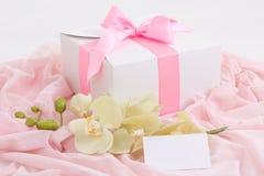 Caja de regalo con la cinta rosada, la orquídea y la tarjeta en blanco Foto de archivo libre de regalías