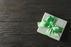 Caja de regalo con la cinta verde en el fondo de madera, visión superior imágenes de archivo libres de regalías