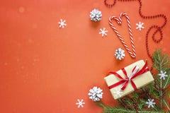 Caja de regalo con las decoraciones de la Navidad en fondo rojo Espacio FO Fotografía de archivo libre de regalías