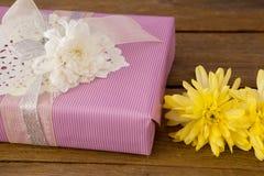 Caja de regalo con las flores en la tabla de madera Foto de archivo