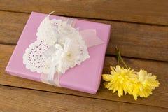 Caja de regalo con las flores en la tabla de madera Foto de archivo libre de regalías