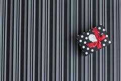 Caja de regalo con las rayas y los guisantes en un fondo rayado foto de archivo