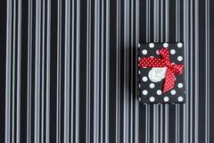 Caja de regalo con las rayas y los guisantes en un fondo rayado fotografía de archivo