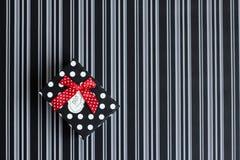 Caja de regalo con las rayas y los guisantes en un fondo rayado imagen de archivo libre de regalías