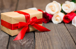 Caja de regalo con las rosas rojas y blancas blured en un backgr de madera oscuro fotos de archivo