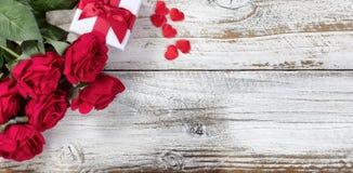 Caja de regalo con las rosas rojas y los corazones en la madera rústica Fotografía de archivo libre de regalías