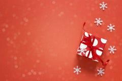 Caja de regalo con los copos de nieve decorativos y espacio para el texto en un rojo Imagen de archivo