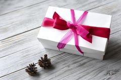 Caja de regalo con un arco en un fondo natural de la madera Imagen de archivo libre de regalías