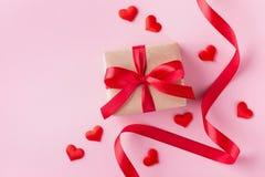 Caja de regalo, corazones y cinta roja en el fondo en colores pastel rosado para la tarjeta de día de San Valentín estilo plano d imagen de archivo
