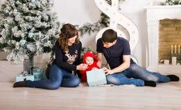 Caja de regalo de la familia de la Navidad actuales, padre de la madre y niño abiertos del bebé en el sitio adornado, sentándose  Fotografía de archivo libre de regalías
