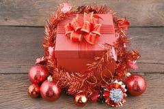 Caja de regalo de la Feliz Año Nuevo con las decoraciones y bola del color en la madera Foto de archivo