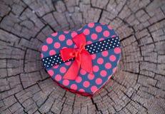 Caja de regalo de la forma del corazón en el tronco de árbol Imagenes de archivo