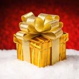 Caja de regalo de la Navidad con el arco que se coloca en nieve fotografía de archivo