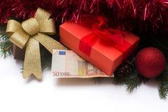 Caja de regalo de la Navidad con el dinero euro en el fondo blanco Foto de archivo libre de regalías