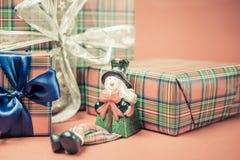 Caja de regalo de la Navidad con el juguete del muñeco de nieve en el fondo rojo Fotos de archivo