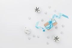Caja de regalo de la Navidad con la cinta azul y cascabel en el escritorio blanco desde arriba Tarjeta de felicitación del día de Imagen de archivo libre de regalías