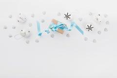 Caja de regalo de la Navidad con la cinta azul y cascabel en el fondo blanco desde arriba Tarjeta de felicitación del día de fies Foto de archivo libre de regalías