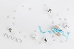 Caja de regalo de la Navidad con la cinta azul y cascabel en el fondo blanco desde arriba Tarjeta de felicitación del día de fies Foto de archivo