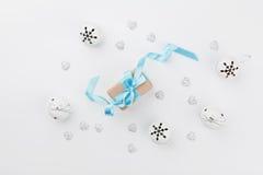 Caja de regalo de la Navidad con la cinta azul y cascabel en la tabla blanca desde arriba Tarjeta de felicitación del día de fies Foto de archivo libre de regalías