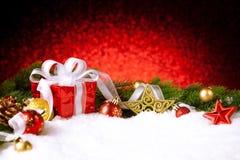 Caja de regalo de la Navidad con las bolas, las estrellas y la decoración en nieve Imagen de archivo libre de regalías