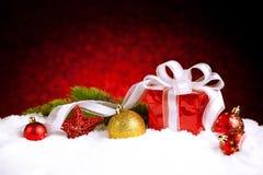 Caja de regalo de la Navidad con las bolas, las estrellas y la decoración en nieve Imagenes de archivo