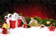Caja de regalo de la Navidad con las bolas, las estrellas y la decoración en nieve Imagen de archivo