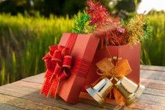 Caja de regalo de la Navidad con las decoraciones en la tabla de madera en puesta del sol Fotografía de archivo